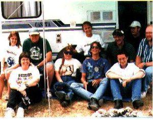 Ten people seated in front of a camper van